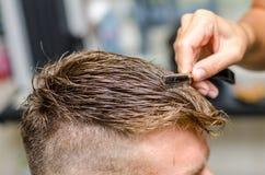 Man& x27 di taglio del parrucchiere; capelli di s con il rasoio dentato Fotografia Stock