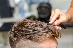 Man& x27 di taglio del parrucchiere; capelli di s con il rasoio dentato Immagini Stock