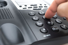 Man dialing a black telephone Stock Photography