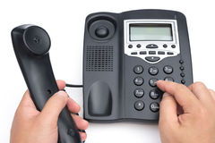 Man dialing a black telephone on white background Royalty Free Stock Photography