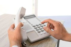 Man dialing number on telephone at table. Indoors royalty free stock photos