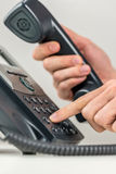 Man dialing out on a landline telephone. Close up view of the hands of a man dialing out on a landline telephone instrument using his finger to punch in the Stock Photo