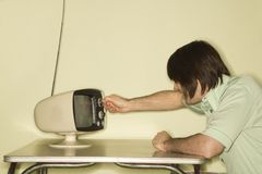 Man dialing television knob. Stock Photos