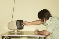 Man dialing television knob. Stock Photos