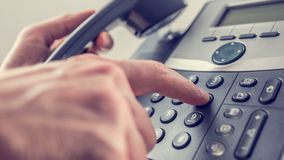 Man dialling out on a landline telephone Royalty Free Stock Image