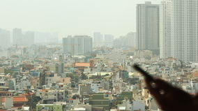 Man dials the phone against the backdrop of the city from the window 3 stock video footage