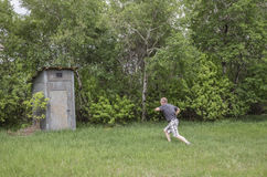 Man with diarrhea running to an out door toilet in the summer. Horizontal image of a man running to the out door toilet nestled in the green bushes on a summer Royalty Free Stock Image