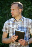 Man with diary outdoor. Man holding diary in a city park Royalty Free Stock Photography