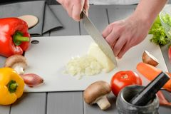Man dicing a bulb onion. And cutting vegetables with a chef`s knife. Cooking vegetables, healthy food and vitamin diet royalty free stock images