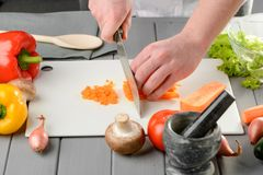 Man dicing carrot. Into small cubes on a white board. Cutting vegetables with a santoku knife. Homemade healthy food stock photo