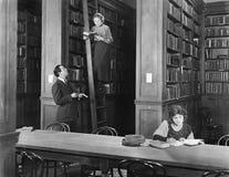 Man die aan een vrouw spreken die zich op een ladder in een bibliotheek bevinden (Alle afgeschilderde personen leven niet langer  stock fotografie