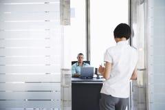 Man die aan Vrouw Status in Bureaudeuropening spreekt Stock Foto's