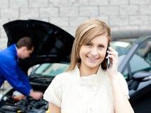 Man die auto van het telefoneren van vrouw herstelt Royalty-vrije Stock Afbeeldingen