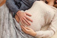 Man die een buik van de vrouwen` s zwangerschap houden stock fotografie