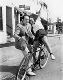 Man die een exuberant vrouw op een fiets proberen in evenwicht te brengen (Alle afgeschilderde personen leven niet langer en geen Royalty-vrije Stock Afbeelding