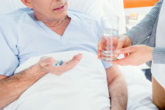 Man die geneesmiddelen en het glas van de vrouwenholding water nemen Stock Foto