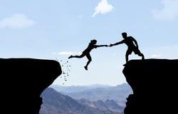 Man die hand bereiken aan vrouw het springen over kloof Stock Afbeelding