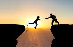 Man die hand bereiken aan vrouw het springen over kloof Royalty-vrije Stock Foto's