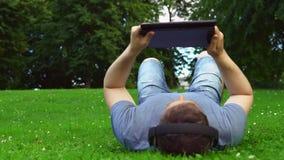 Man die in het park ligt en een tablet-pc gebruikt stock footage