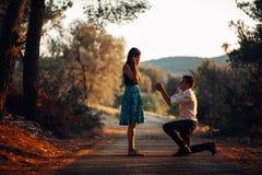 Man die in liefde een verraste, geschokte vrouw voorstellen om hem te huwen Voorstel, overeenkomsten en huwelijksconcept betrotha Royalty-vrije Stock Afbeeldingen