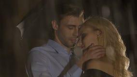 Man die mooie jonge vrouw strelen onder paraplu op regenachtige avond, aantrekkelijkheid stock video