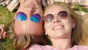 Man die teder vrouw op wang kussen, samen liggend op gras die, op blauwe hemel letten stock footage