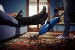 Man die terwijl vrouw die karweien thuis doet ontspant royalty-vrije stock afbeelding