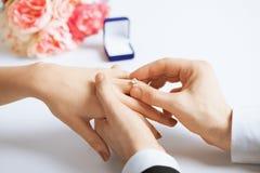Man die trouwring op vrouwenhand zetten royalty-vrije stock afbeelding