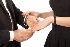 Man die trouwring op vrouwenhand zetten stock foto's