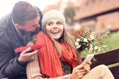 Man die verrassingsgift geven aan vrouw in het park stock fotografie