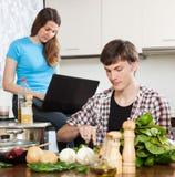 Man die voedsel voorbereiden terwijl vrouw die laptop bekijken Royalty-vrije Stock Afbeeldingen