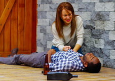 Man die vrijetijdskleding gedronken liggen dragen uit overgegaan op houten oppervlakte, mooie vrouwenzitting naast hem die prober stock foto's