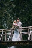 Man die vrouw op houten brug in berg koesteren Royalty-vrije Stock Foto