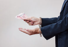 Man dient handcuffs en geld in zijn palmen in Stock Foto