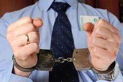 Man dient handcuffs met geld in zijn zak in Royalty-vrije Stock Foto's