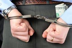 Man dient handcuffs met geld in zijn zak in Stock Afbeelding