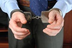 Man dient handcuffs vóór zich in Stock Foto