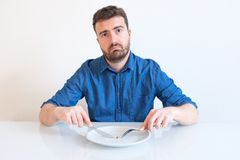 Man on diet feeling hungry and bored by vegetable meal. Hungry man feeling sad in front of a dish with a cabbage Stock Photography