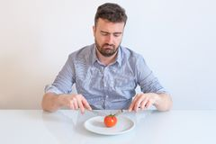 Man on diet feeling hungry and forced to eat vegetable meal. Hungry man feeling angry in front of a dish with a tomato Royalty Free Stock Images
