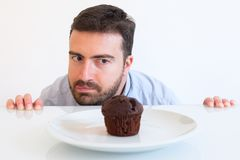 Man on diet in temptation by sweet muffing Royalty Free Stock Photos