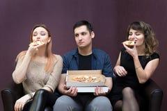 Man dieting looks like girlfriends eat pizza. stock image