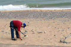Man digging for coins on a beach. Stock Image