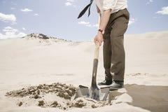 Man digging in desert Stock Image