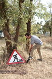 Man digging near the sign. Forbidden to dig stock image