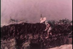 Man digging trench in river stock footage