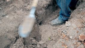 Man digging a trench with a spade. With only his feet visible stock video footage