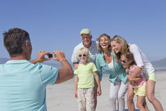 Man with digital camera photographing multi-generation family on sunny beach Royalty Free Stock Photography