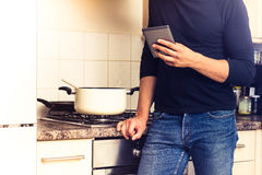 Man with digital reader in kitchen Royalty Free Stock Photography