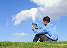 Man with digital tablet. Businessman with digital tablet sitting down on grass Royalty Free Stock Photo