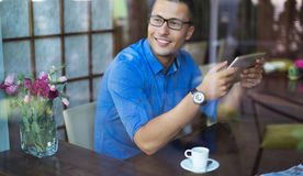 Man with digital tablet in coffee shop Stock Image